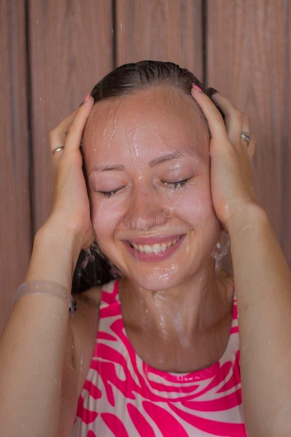 微笑在阵雨的年轻美丽的女孩 库存照片