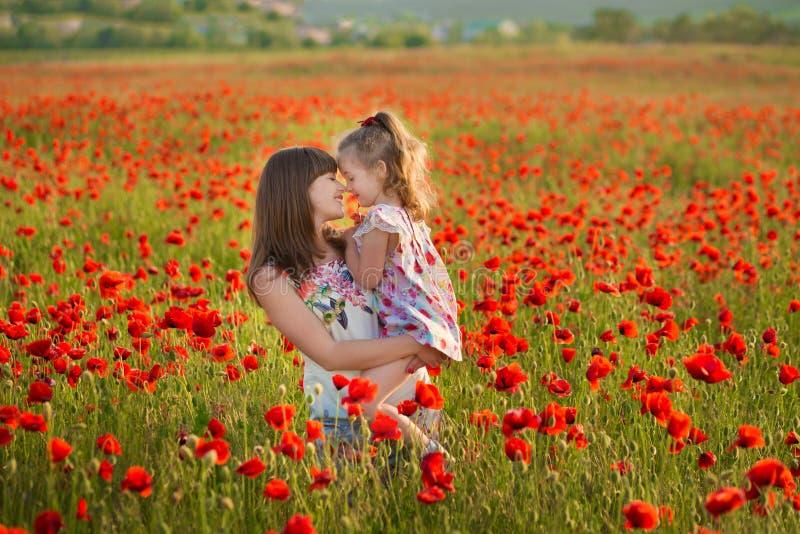微笑在鸦片的母亲和女儿调遣 在鸦片领域的野餐 与家庭的步行在鸦片领域 推车鸦片 免版税库存照片
