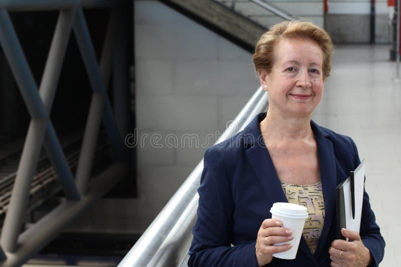 微笑在经典火车、机场或者地铁站的可爱的成熟的商业妇女通勤者画象在城市,拿着coffe 免版税图库摄影