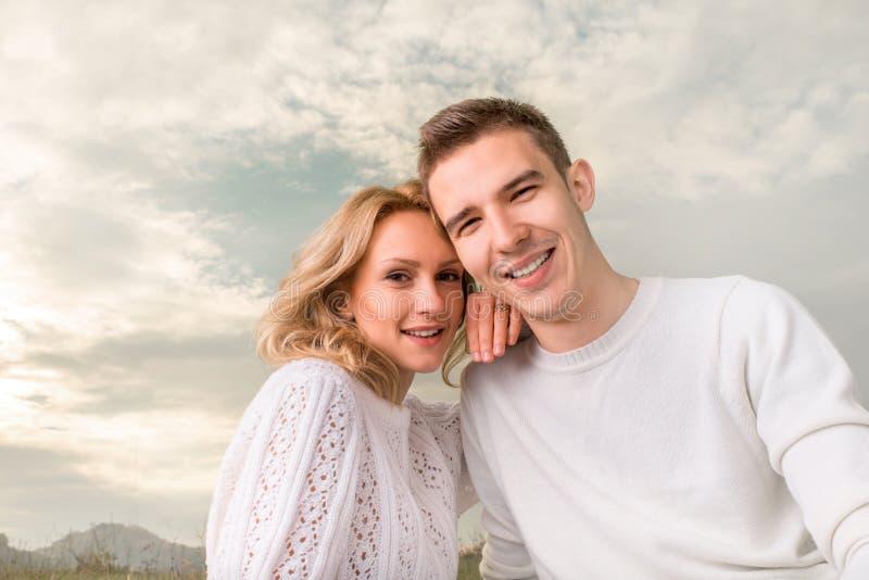 微笑在晴朗的天空下的愉快的夫妇 免版税库存图片