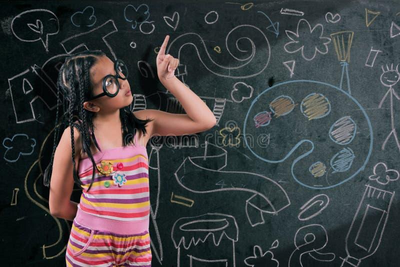 微笑在黑板前面的聪明的小女孩 免版税库存照片