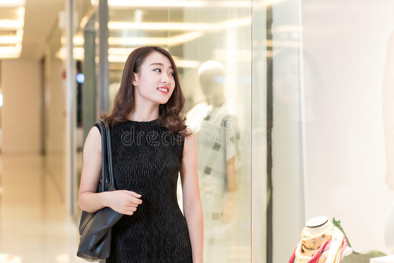 微笑在购物窗口前面的一个美丽的亚裔夫人 免版税库存照片