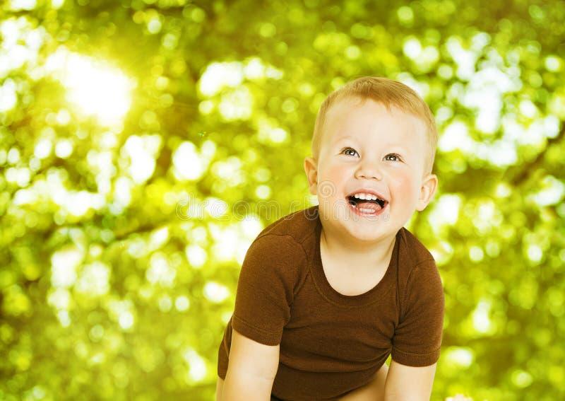 微笑在绿色背景的愉快的孩子 关闭婴孩portrai 图库摄影
