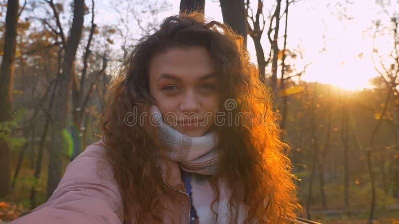 微笑地观看入照相机和闪光对它的卷发的白种人女孩Selfie照片在晴朗的秋季公园 库存照片