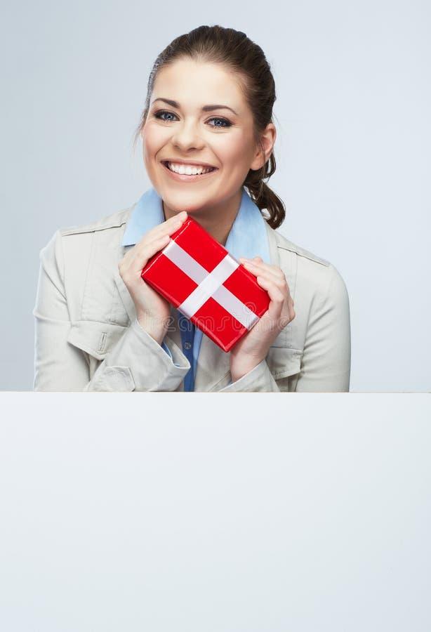 微笑女商人举行红色礼物盒 免版税图库摄影