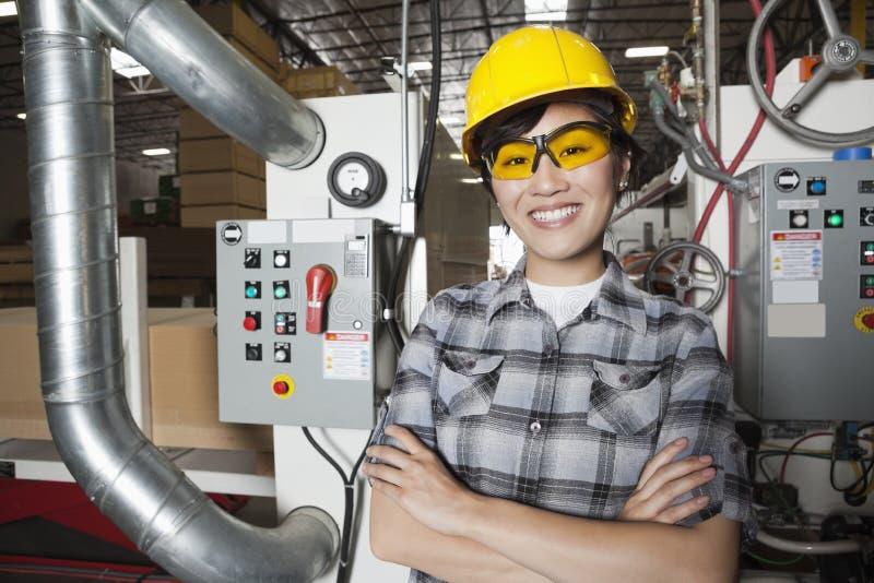 微笑女性的产业工人画象,当站立在有机器的工厂在背景中时 库存照片