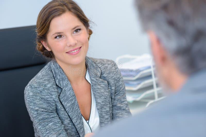 微笑女性的办公室工作者谈话和 库存图片