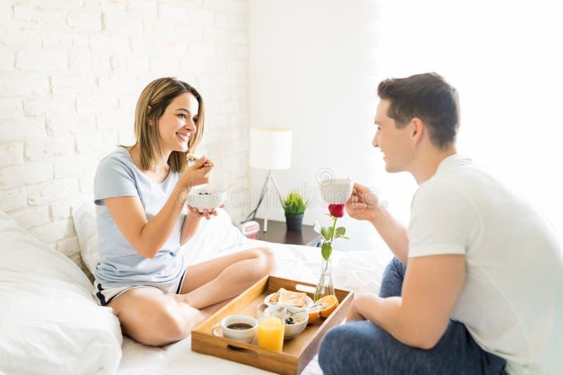微笑女性食用谷物,当看在床上时的男性 图库摄影
