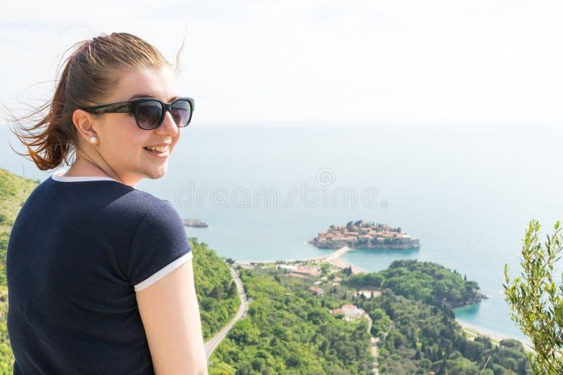 微笑对与太阳镜的照相机的愉快的少女在布德瓦黑山山,享用圣斯特凡岛和亚得里亚 库存图片