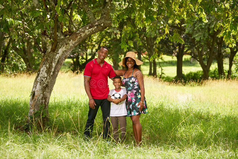 微笑对与橄榄球的照相机的母亲父亲和孩子 免版税库存照片