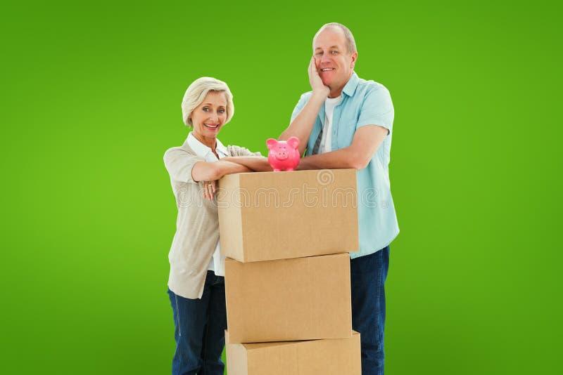 微笑对与移动的箱子和存钱罐的照相机的更旧的夫妇的综合图象 图库摄影