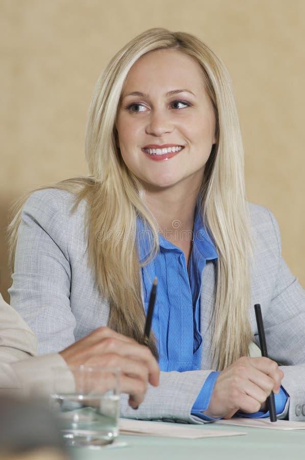 微笑对会议桌的女实业家 库存照片