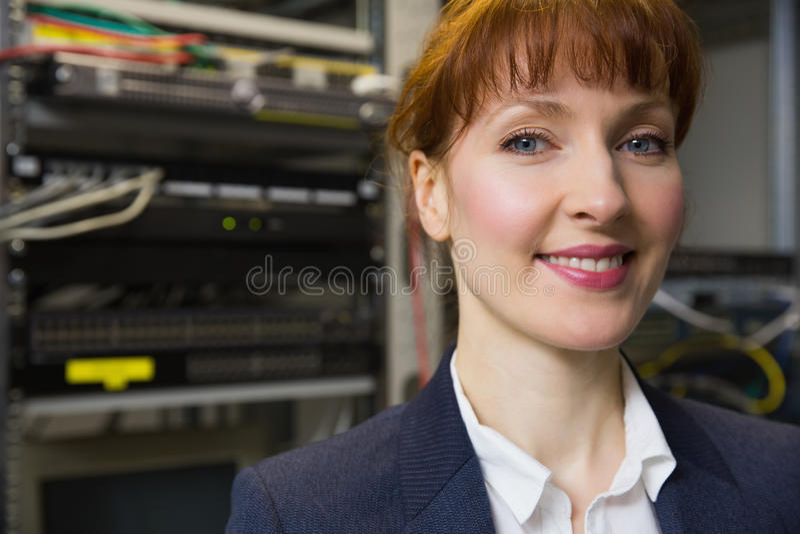微笑对在开放服务器旁边的照相机的俏丽的技术员 免版税库存照片