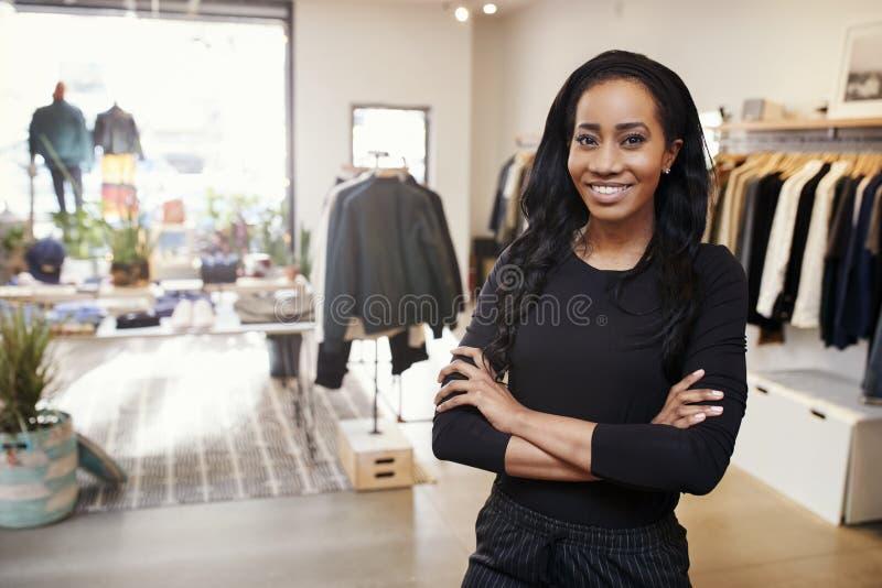 微笑对在服装店的照相机的年轻黑人妇女 图库摄影