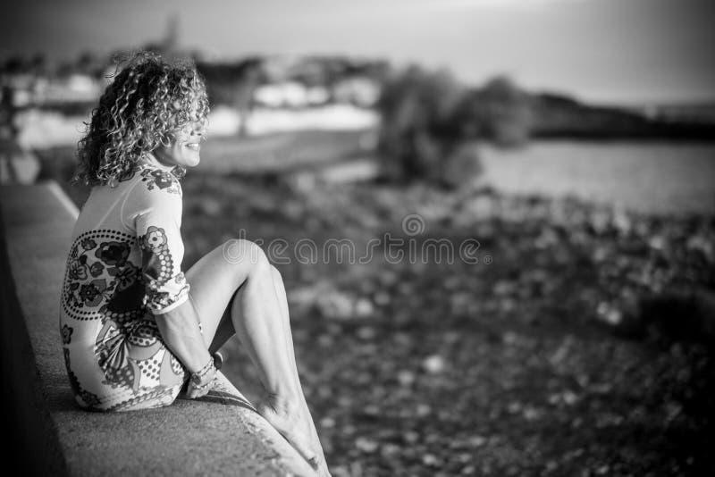 微笑对在海滩前面的日落的美好的快乐的式样中年 假期和享受室外活动妇女 免版税库存照片