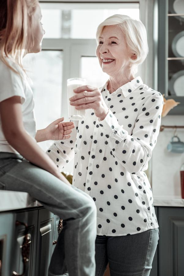 微笑对女孩的正面时髦的老婆婆,当给她的一些牛奶时 免版税库存照片