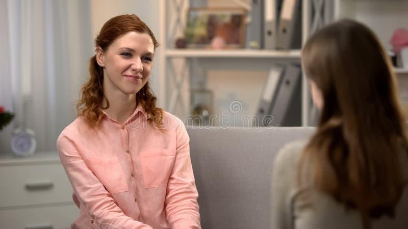 微笑对女性朋友的俏丽的年轻女人,谈话在沙发,陪伴 免版税库存照片