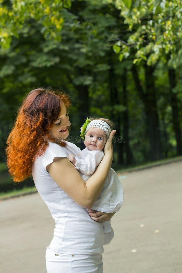 微笑对她的小女儿的红发妇女 白色礼服、袜子和被编织的头饰带的女孩在公园 图库摄影