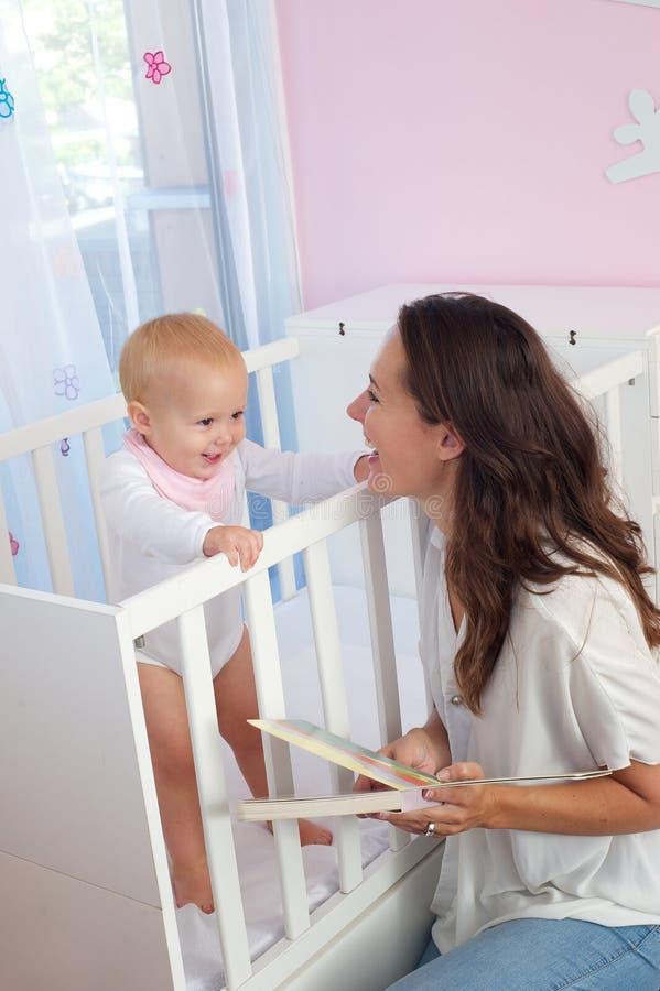 微笑对小儿床的婴孩的愉快的母亲 库存照片