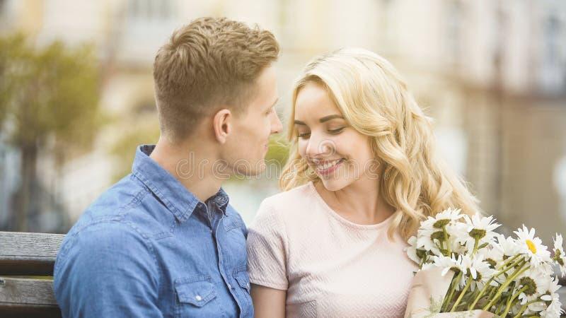 微笑对心爱的人的美丽的白肤金发的女孩,拿着好的花 免版税库存照片