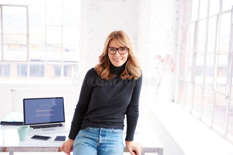 微笑对您和看照相机的确信的女实业家,当站立在办公室时 库存照片