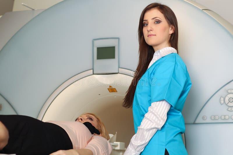 微笑对成熟女性患者的放射性技术员说谎在CT扫描床上 免版税库存图片