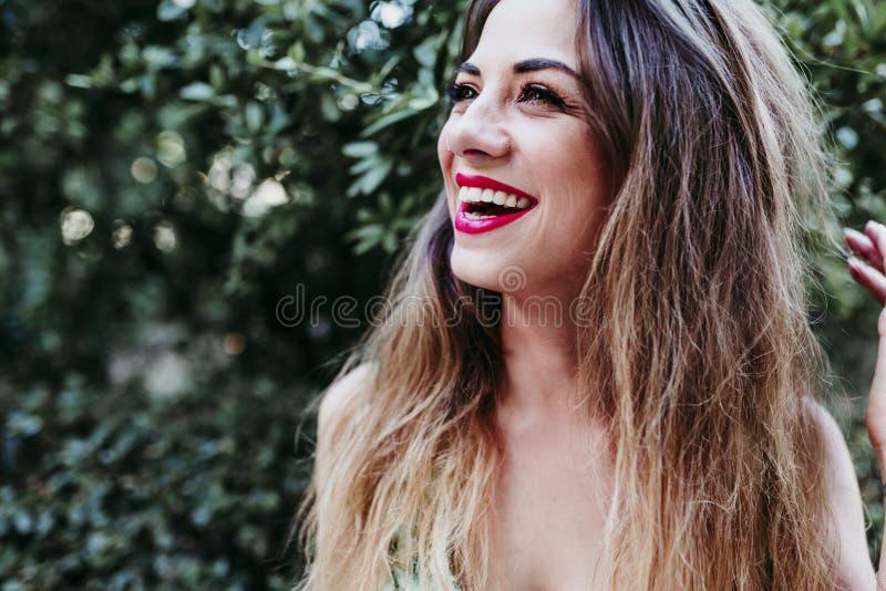 微笑对日落的美丽的白肤金发的年轻女人画象  红色嘴唇和华美的微笑 r 库存图片