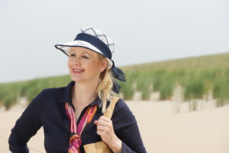 微笑对海滩的一个美丽的老妇人的画象 免版税库存照片