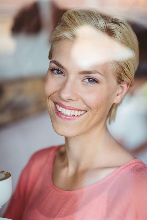 微笑对照相机和拿着一杯咖啡的愉快的白肤金发的妇女 免版税库存图片