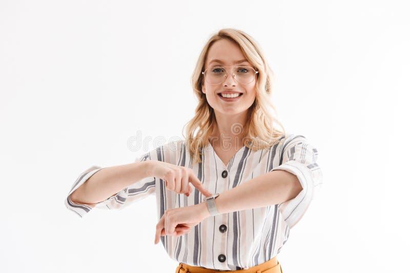 微笑对照相机和指向在手表的乐观迷人的妇女戴着眼镜照片  图库摄影