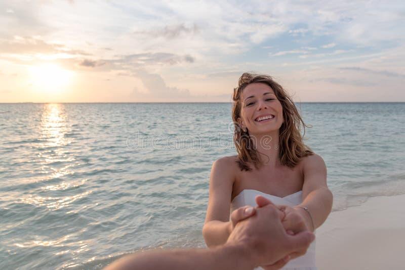 微笑对照相机和握他的在海滩的年轻女人男朋友手在日落期间 图库摄影
