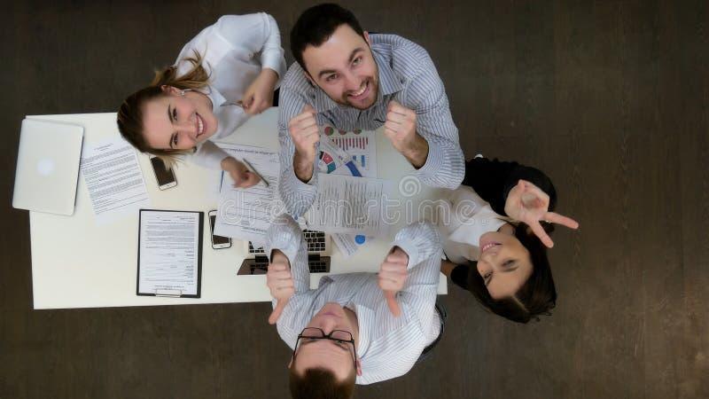 微笑对照相机和显示赞许的愉快的办公室工作者 免版税库存图片