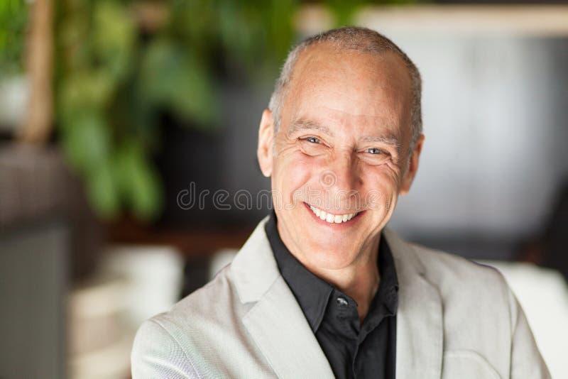 微笑对照相机的一个成熟人的画象 年长愉快的人 免版税库存图片