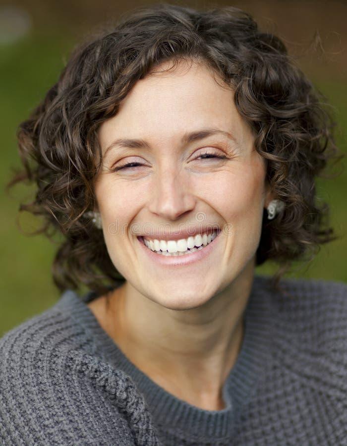 微笑对照相机的一名成熟妇女的特写镜头 免版税图库摄影