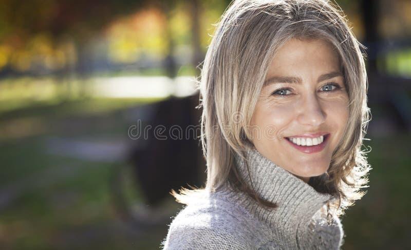 微笑对照相机的一名成熟妇女的画象 灰色头发 免版税库存图片