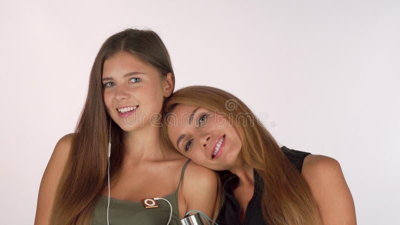 微笑对照相机的两个美丽的女性朋友,摆在锻炼衣物 免版税库存图片