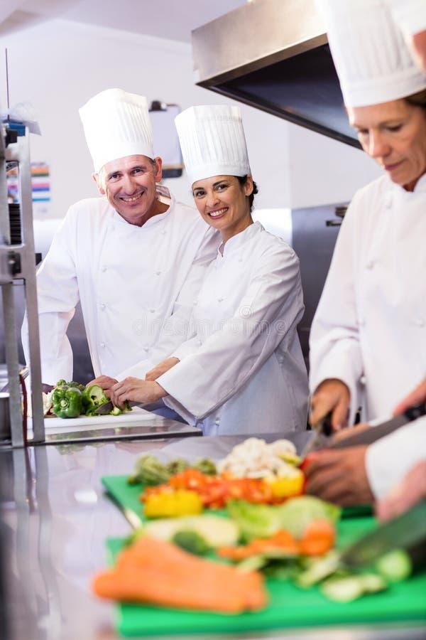 微笑对照相机的两位厨师,当砍菜时 免版税库存图片