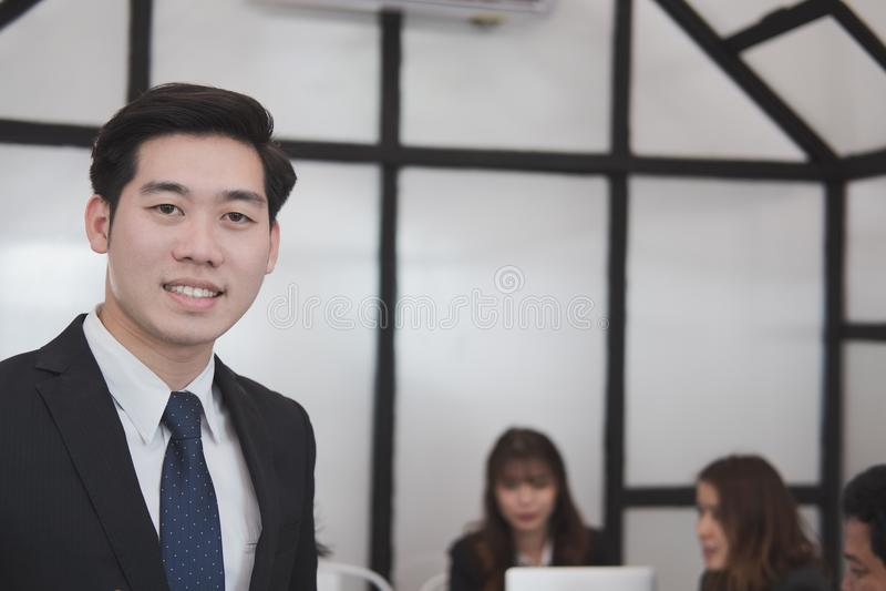 微笑对照相机的亚洲商人,当同事有meetin时 库存图片