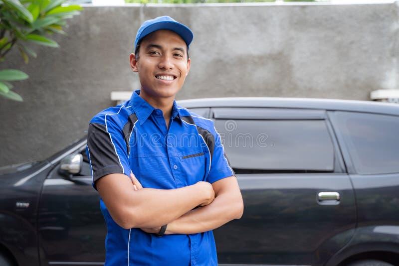 微笑对照相机的亚裔汽车修理师 库存图片