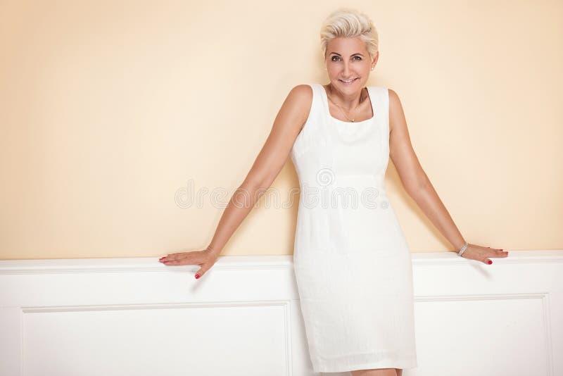 微笑对照相机的典雅的白肤金发的夫人 库存图片