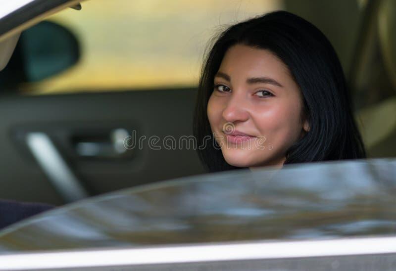微笑对照相机的友好的年轻女人司机 免版税库存图片