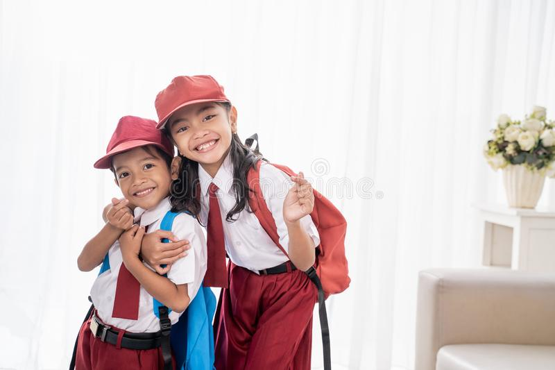 微笑对照相机的可爱的两小学生 免版税库存照片