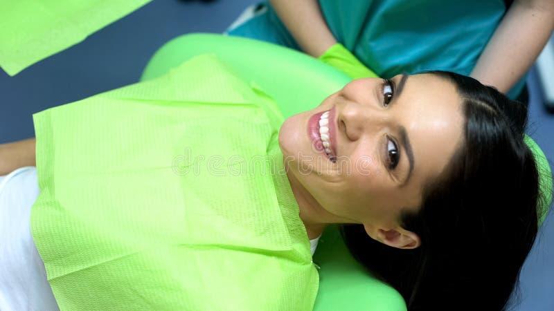 微笑对照相机的夫人在成功的牙科操作,专业关心以后 免版税图库摄影