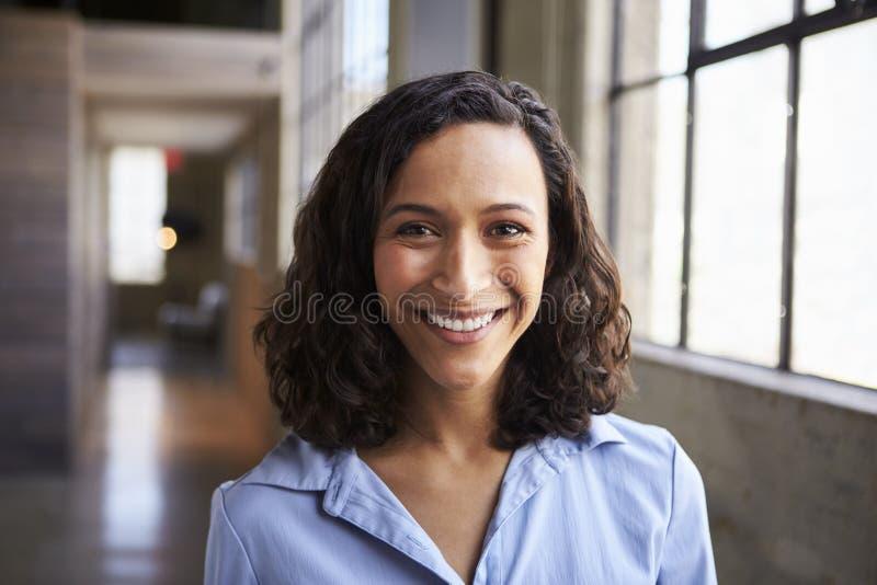 微笑对照相机的年轻混合的族种女实业家 免版税库存图片