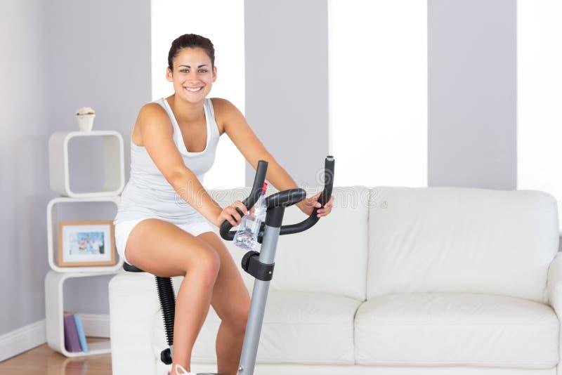 微笑对照相机的快乐的亭亭玉立的妇女,当训练在锻炼脚踏车时 免版税图库摄影