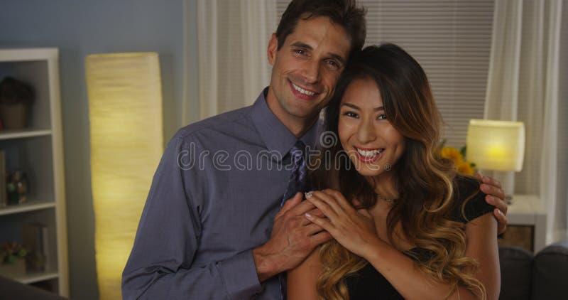 微笑对照相机的愉快的人种间夫妇 免版税库存图片