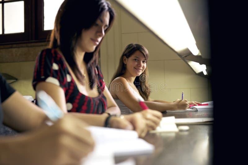 微笑对照相机的愉快的女学生在大学图书馆里 免版税库存照片