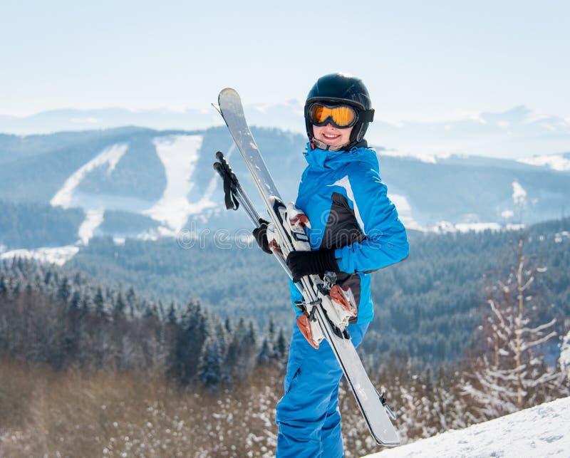 微笑对照相机的愉快的女性滑雪者,拿着她的滑雪、佩带的蓝色滑雪服和黑盔甲对冬天滑雪场 库存图片