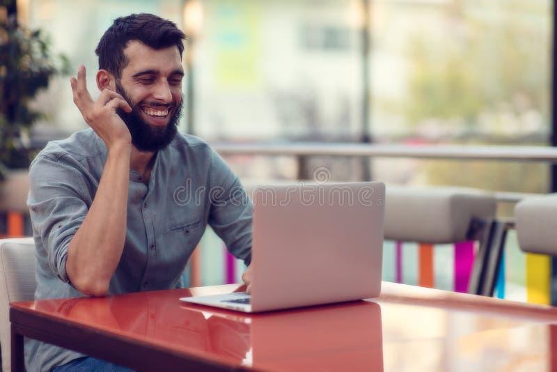 微笑对照相机的成功的有胡子的设计师半身画象,当工作在自由职业者在netbook时 免版税库存照片
