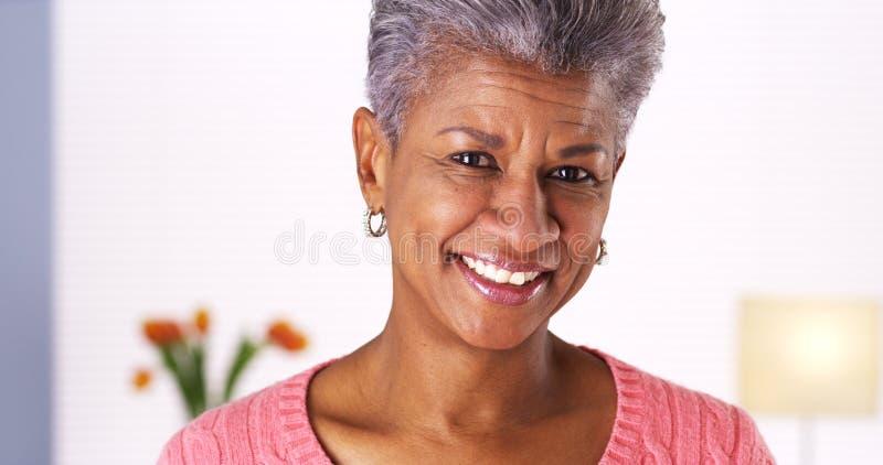 微笑对照相机的成熟非洲妇女 免版税库存图片